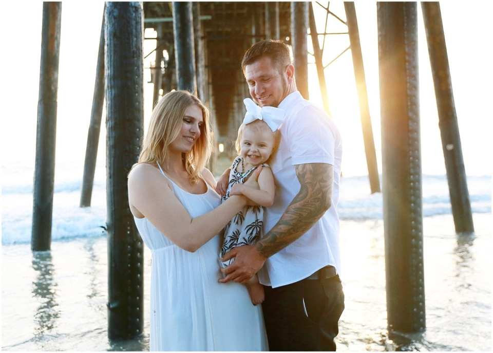 family photo session at beach laughing with baby wearing white classic outfits