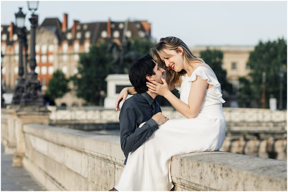 woman kissing husband along Pont Neuf bridge Paris