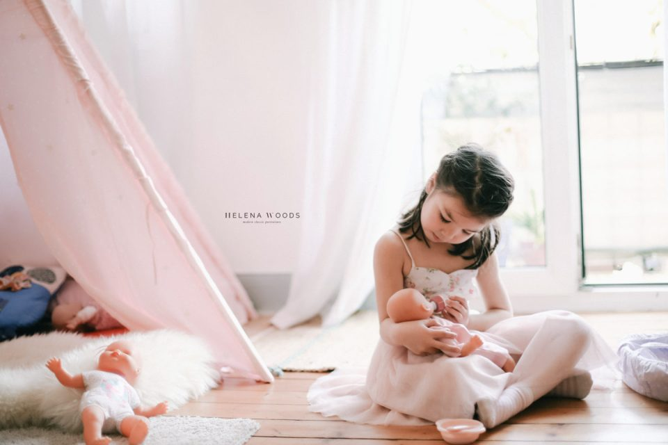 girl feeds baby doll with lifestyle family photographer Helena Woods Photography