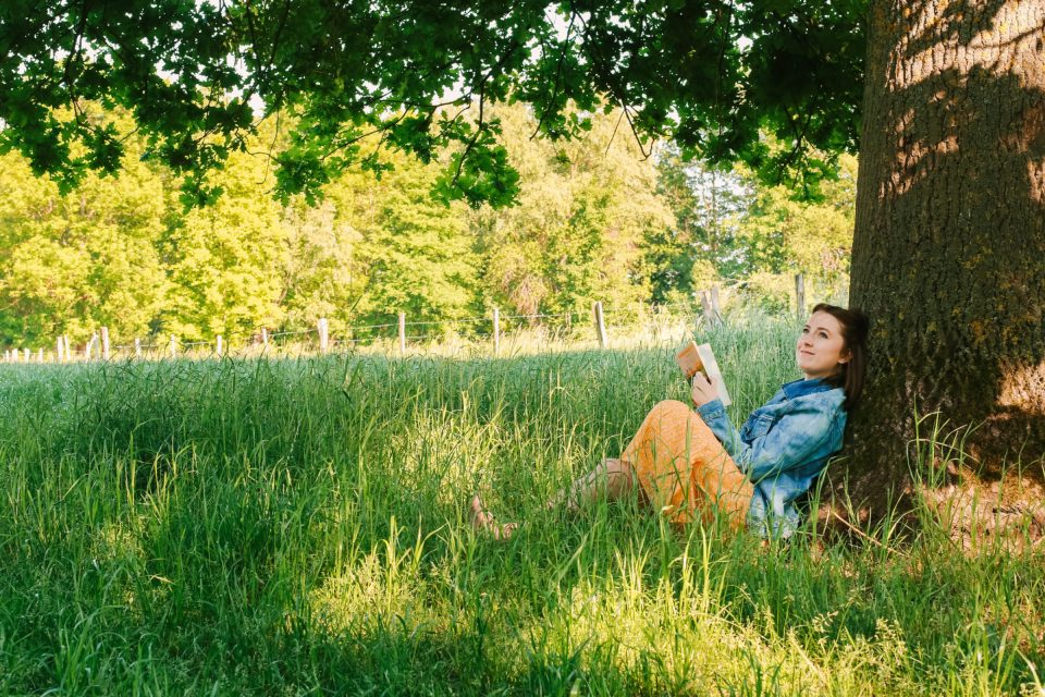 girl reading against tree sharing how to hygge in summer