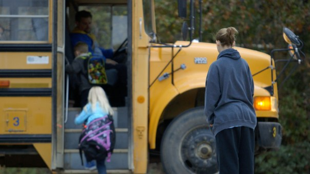 Shawna Baldwin, sex offender, watches her children board a school bus.