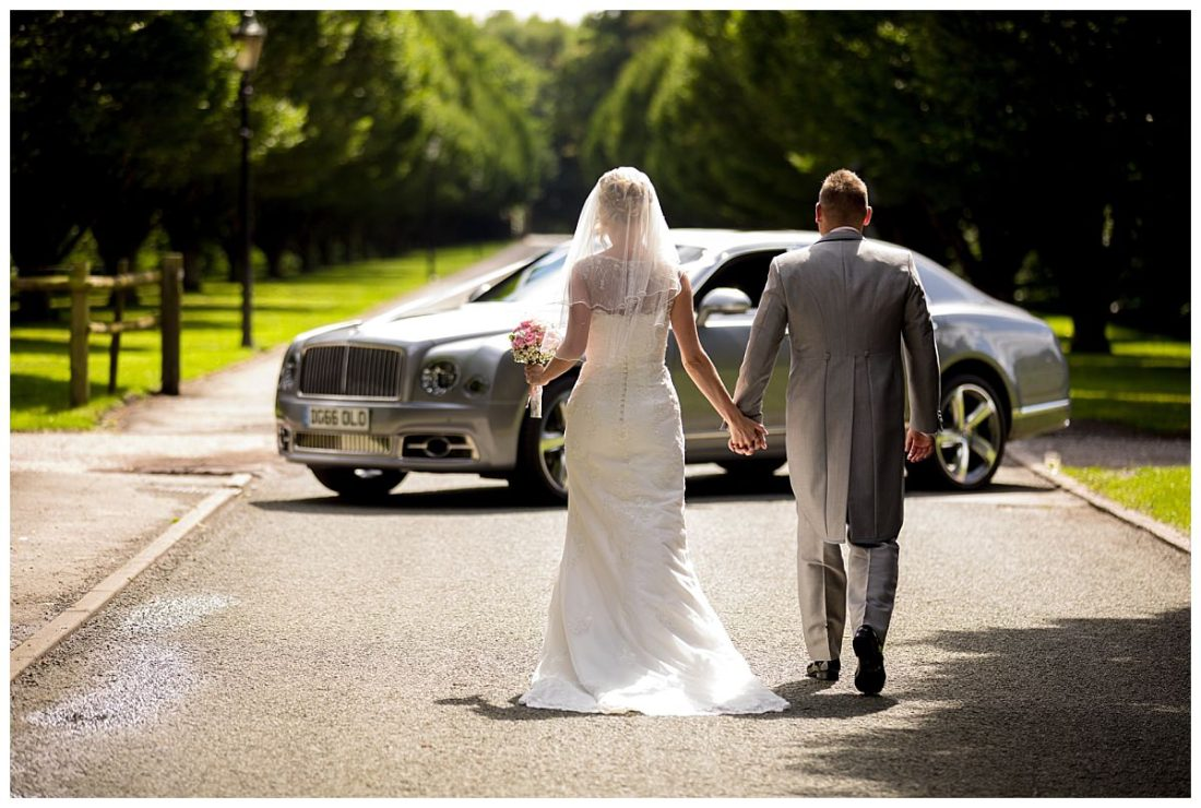 Bride and groom walking down Crewe Hall drive