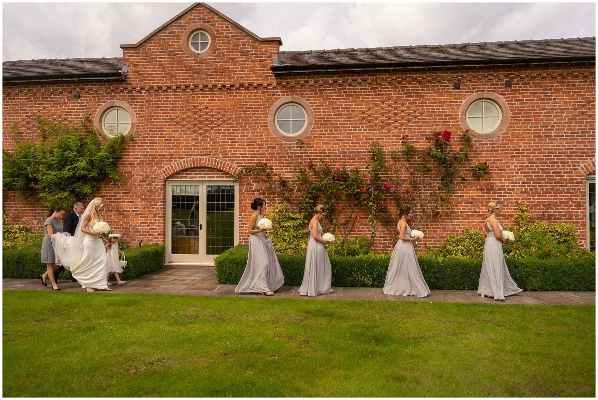 Bride and bridesmaids walking to wedding ceremony at Merrydale Manor