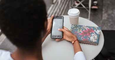 unrecognizable black woman messaging on phone at cafe