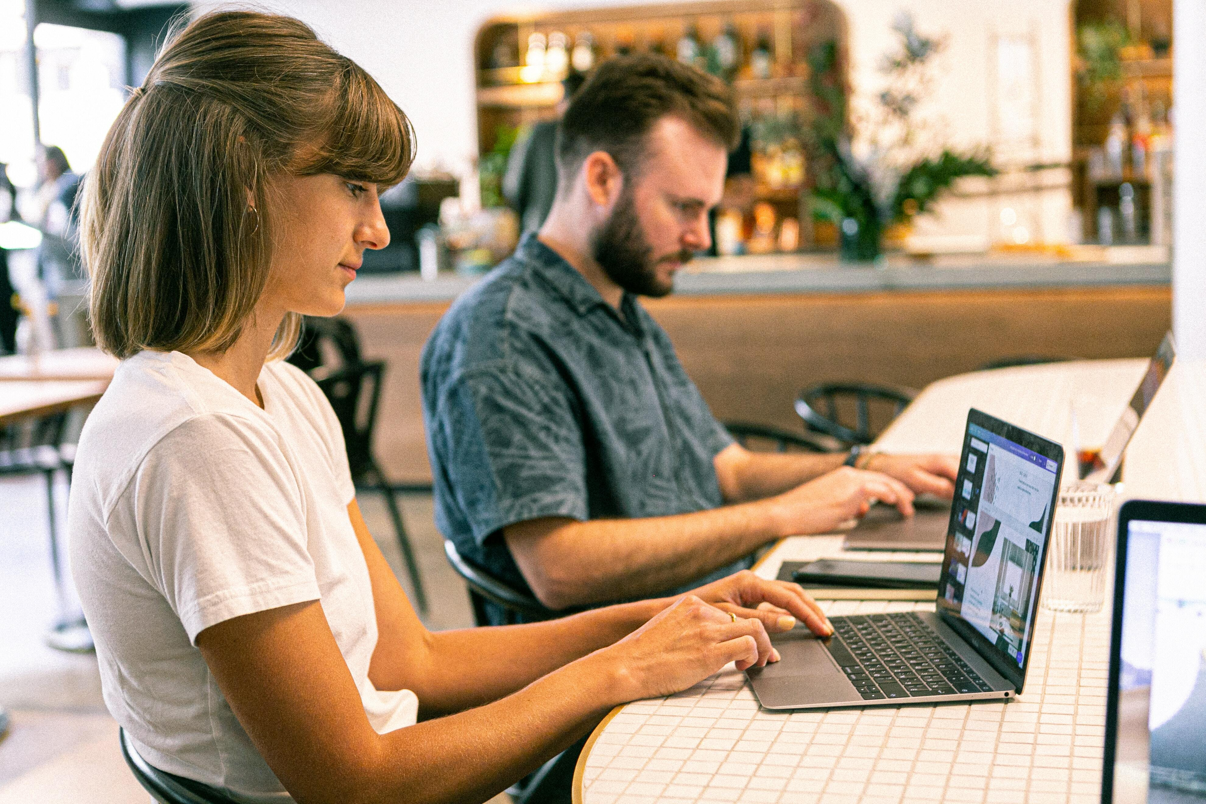 Outsource your social media, newsletters, and other work to this handy AI tool. Pictured: A man and a woman type on laptops.