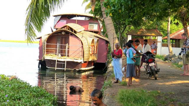 Vår kanalbåt til kai. Mannen i front vasker seg i det passe skitne vannet, mens mannen i midten fanger fisk med bare hendene.