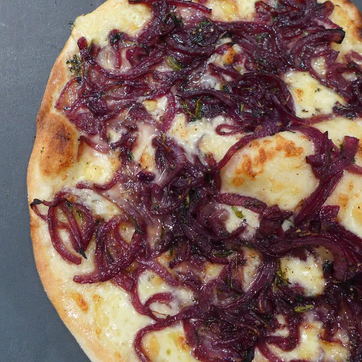 Pizza med rødvinskokt løk.