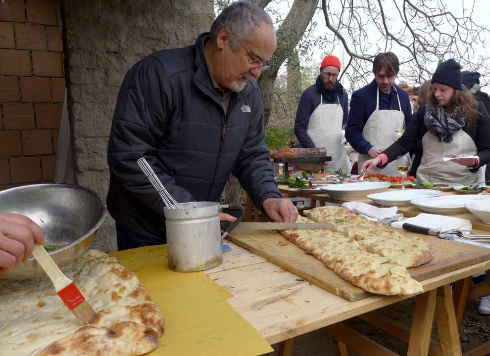 Noen pensler pizzaene og noen skjærer ferdig rosmarinpizza som skal serveres sammen med herlige råvarer.