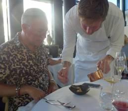 Esben Holmboe Bang serverer selv ved bordet. Her øses husets egen kombucha over rå kamskjell med rips og rogn. Høyrøkt skorsonerrotkrem under.