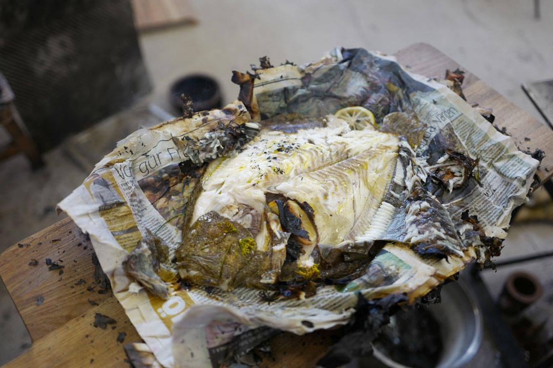 Luqaz skreller forsiktig av skinnet på fisken, og under ser vi det perfekte fiskekjøttet.