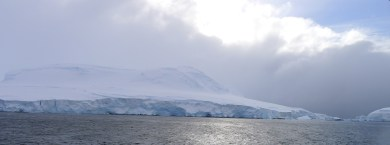 An island in the Antarctic Peninsula covered by snow and ice, right next to our last coring location in Crystal Sound