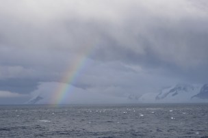 A rainbow formed on the sea surface as it was raining