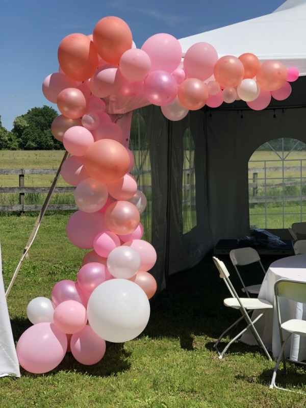 Completed balloon arch kit hung on white tent.