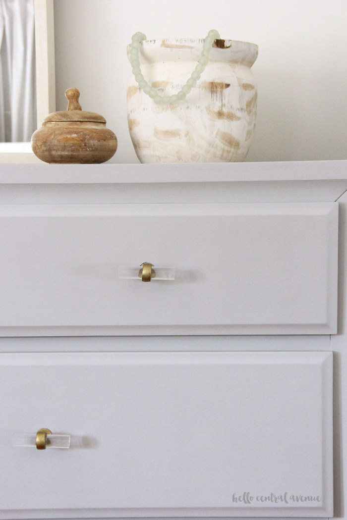 An affordable gold curtain rod and new acrylic drawer pulls are a great way to update your master bedroom!