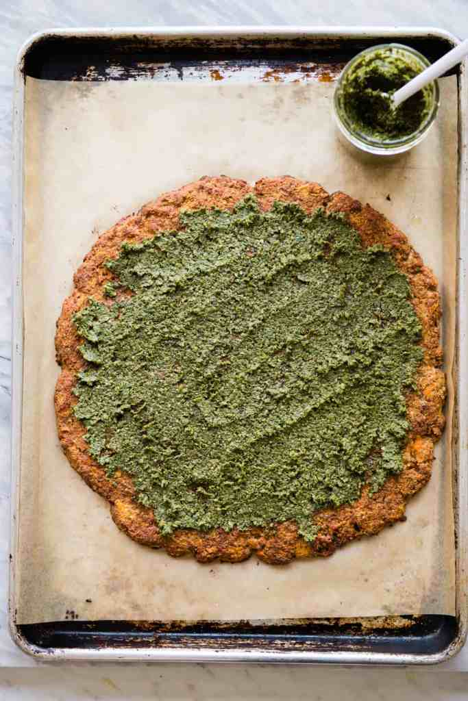 Arugula-topped pesto pizza made with grain-free sweet potato crust