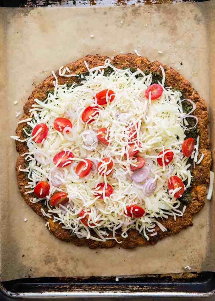 Arugula-topped pesto pizza made with grain-free sweet potato crust