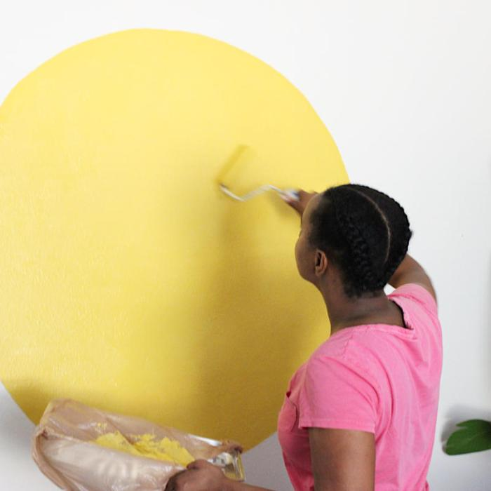 Black girl in pink shirt paints bright yellow circle on a wall with a roller.