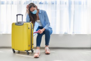 Woman traveler in face protective mask affected by flight delay and cancelled travel and vacation. Travel ban due to coronavirus outbreak and covid-19 ncov virus epidemic