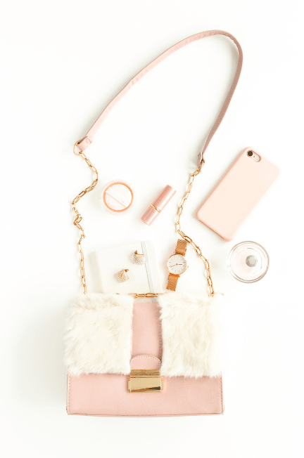 white and pink purse and contents against white background