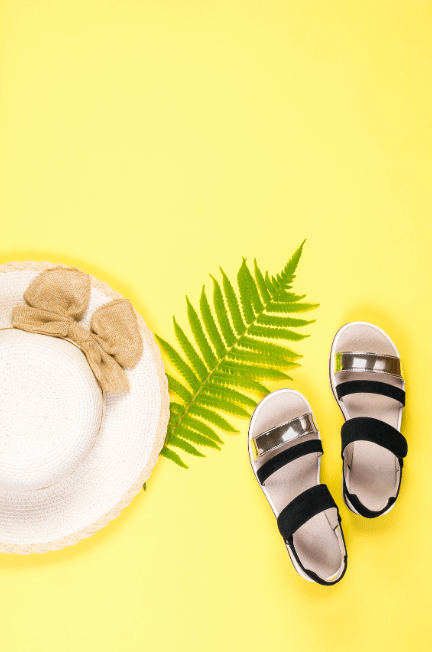 black strap sandals on a yellow background with white sun hat on the left-hand side