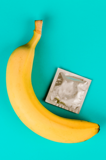 A banana and a condom seductively posed over a turquoise blue background