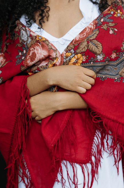 Close up of a red shawl wrapped between hands