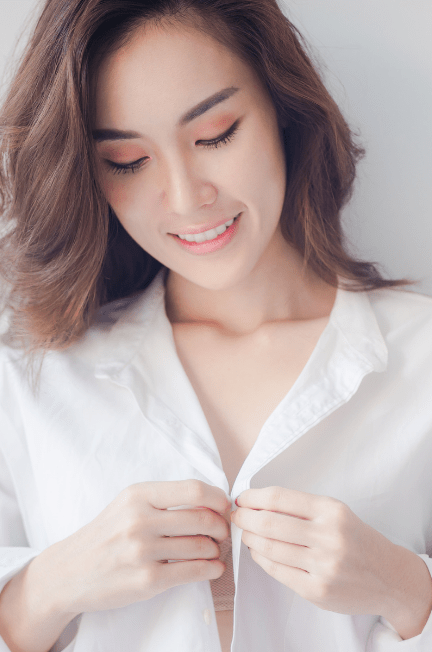 Woman buttoning up a white shirt