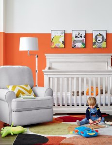 A bright gender neutral nursery and baby room, featuring orange paneled walls, white crib, dove grey reclining chair and animal art prints