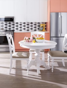 modern kitchen shown with slick appliances, white table and peach cabinetry
