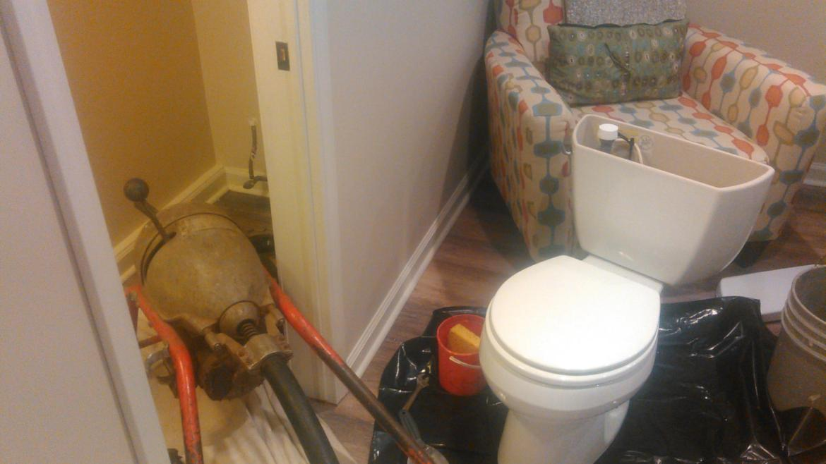 drain cleaning electric eel sewer machine in bathroom toilet has been lifted and sitting to the right to enable snaking through toilet flange