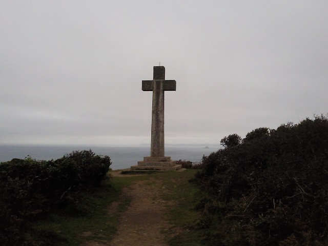 A granite cross standing on a cliff top.