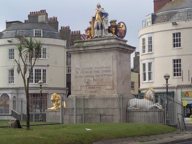 """A statue of George III on a pedestal, flanked by a lion and a unicorn. An inscription reads: """"The gratefil inhabitants to GEORGE THE THIRD on entering the 50th year of his REIGN"""""""
