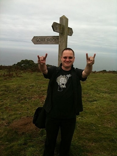 A signpost pointing to Goat Rock. In front of it stands a man dressed in black (the Helpful Mammal), doing the heavy metal devil horns sign.