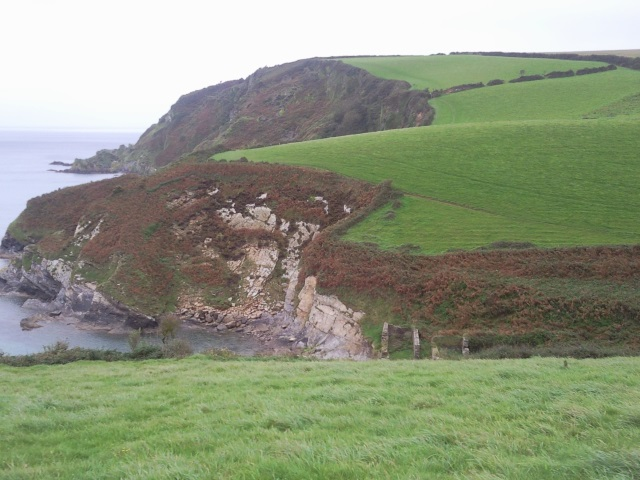 Looking along the coast, a series of hills are ahead with the ruins of a building in the nearest valley