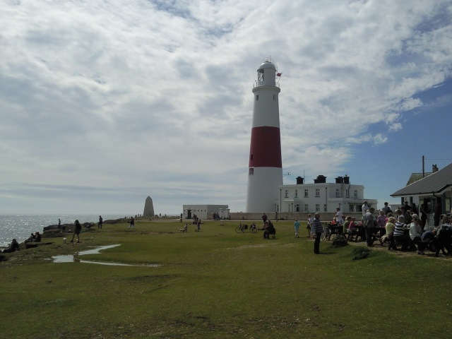 A white lighthouse with a central red band