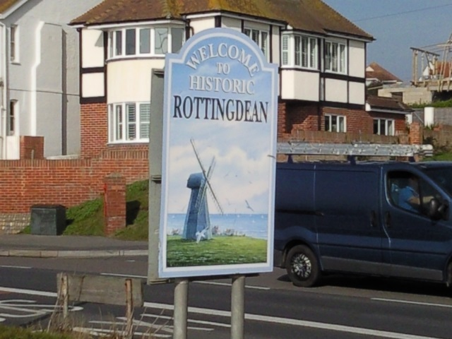 """Sign: """"Welcome to Historic Rottingdean"""" with a picture of Rottingdean's windmill."""