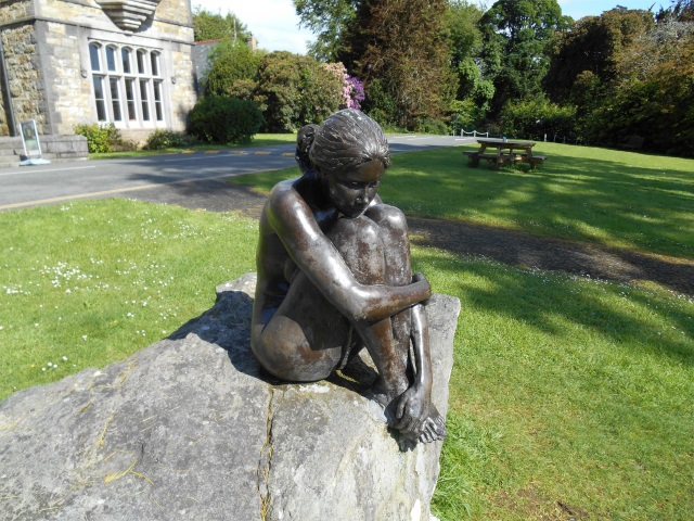 Bronze statue of a girl sitting on a rock, her arms clasped around her knees