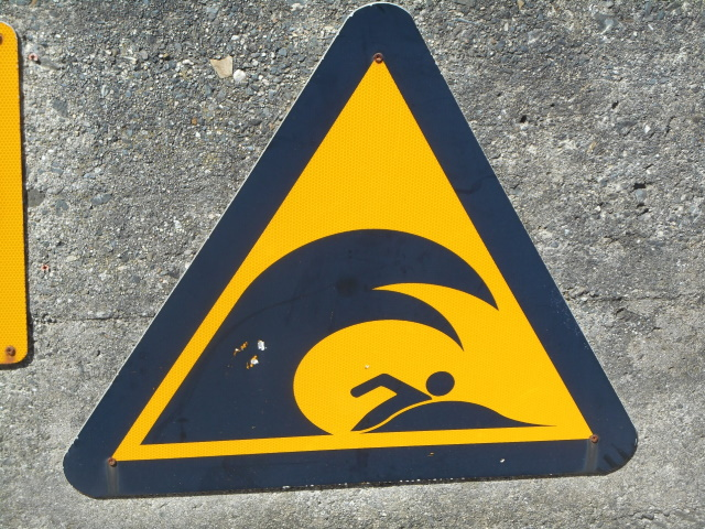 A sign warning of large waves.w.
