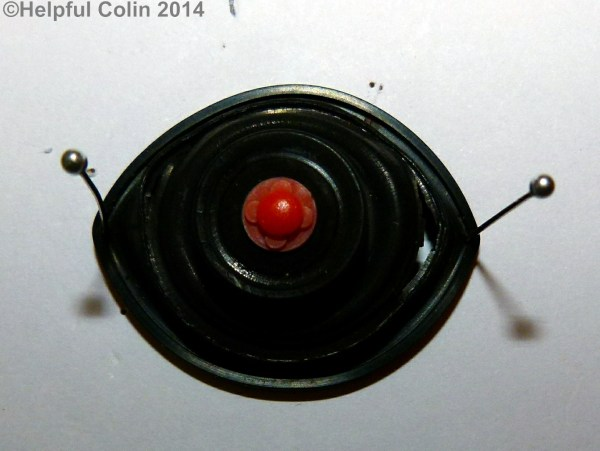 A Damaged Diaphragm from Toilet Silent Fill Valve. It's stretched to make it oval and pinned to a board to expose the splits in the rubber.