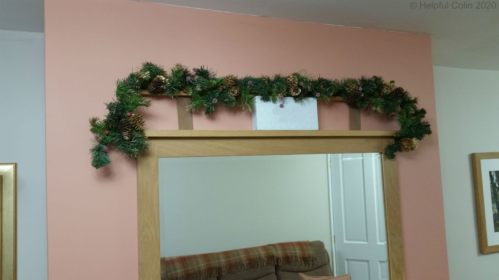 garland-frame being slotted behind a mirror