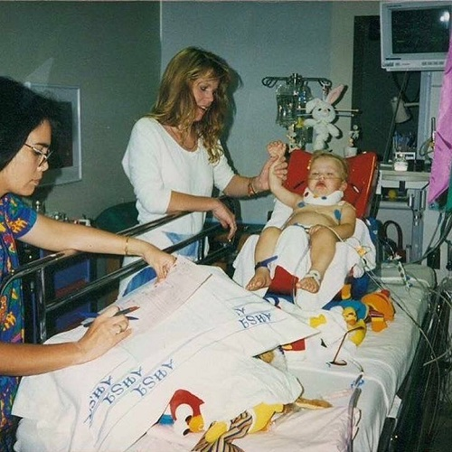 Photo of Patrick Ivison as a child being taken care of at the hospital, sitting on a hospital bed, being assisted by a nurse and his mother.