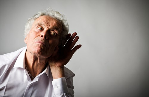 Picture of a man with his hand to his ear.