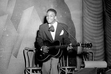 Unidentified man playing guitar inside club, circa 1950. Paul Henderson, HEN.00.A2-248.