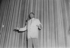 Unidentified man at microphone on stage, circa 1952. Paul Henderson, HEN.00.A2-261.