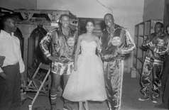 Two unidentified Harlem Globetrotter basketball players posing with unidentified woman in formal dress, circa 1957. Paul Henderson, HEN.00.A2-263.