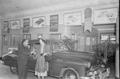 Unidentified man and woman inside automobile showroom, circa 1949. Paul Henderson, HEN.00.B1-117.