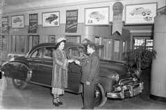 Unidentified man and woman inside automobile showroom, circa 1949. Paul Henderson, HEN.00.B1-118.