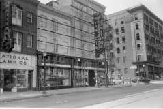 Shows National Lamp Company, Stanley's Furniture, Amoco Gas Station, Henry W. Checket and Company Clothing and Furniture store, pedestrians, automobiles. Scaffolding on Stanley's Furniture. Eutaw Street and Mulberry Street, Baltimore, circa 1952. Paul Henderson, HEN.00.B1-144.