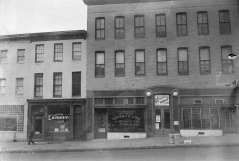 """Shows Charlie Hom Laundry, West Baltimore District Office Supreme Liberty Life Insurance Company of Chicago, Illinois, sign for dancing """"Juke Box Hop Dancing,"""" J. Arnell Frisby Real State Insurance Accounting and Auditing, pedestrian on sidewalk, circa 1950. Paul Henderson, HEN.00.B1-146."""