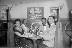 Three men and one woman seated in restaurant or bar booth with Arrow Beer. Possibly advertisement for Arrow Beer, circa 1951. Paul Henderson, HEN.00.B2-216.